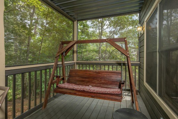 Swing on a covered porch at Amazing Memories, a 3 bedroom cabin rental located in Pigeon Forge