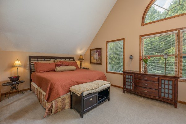Bedroom with a king bed, two lamps, two tables, and a dresser at Amazing Memories, a 3 bedroom cabin rental located in Pigeon Forge