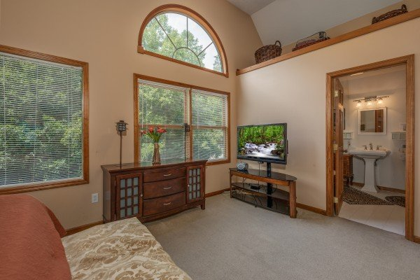 Dresser, tv, and en suite bath at Amazing Memories, a 3 bedroom cabin rental located in Pigeon Forge