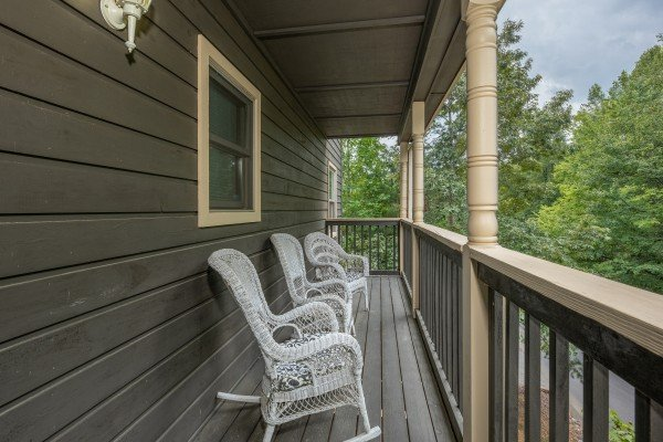 Wicker rocking chairs on a covered deck at Amazing Memories, a 3 bedroom cabin rental located in Pigeon Forge