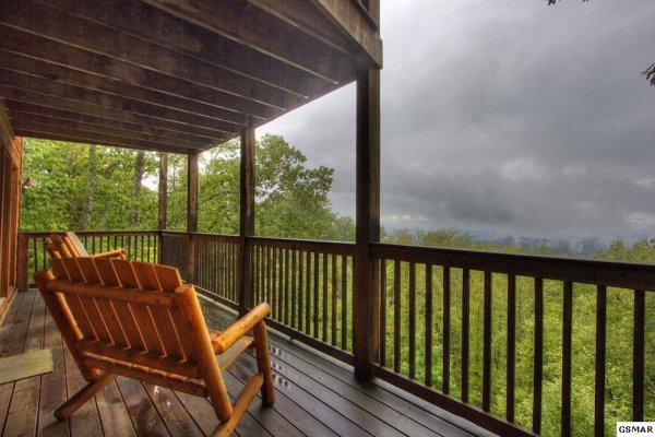 Oversized rocking chairs on a covered deck at Serenity Heights, a 3 bedroom cabin rental located in Pigeon Forge