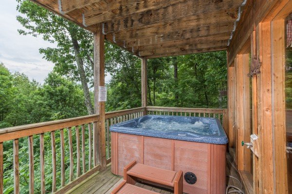 Hot tub on a covered deck at Serenity Heights, a 3 bedroom cabin rental located in Pigeon Forge