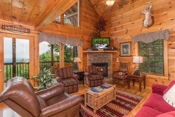 Living room with fireplace, TV, and deck accessat Serenity Heights, a 3 bedroom cabin rental located in Pigeon Forge