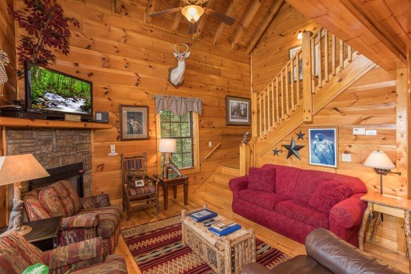 Living room with fireplace, TV, and access to the upper floor at Serenity Heights, a 3 bedroom cabin rental located in Pigeon Forge
