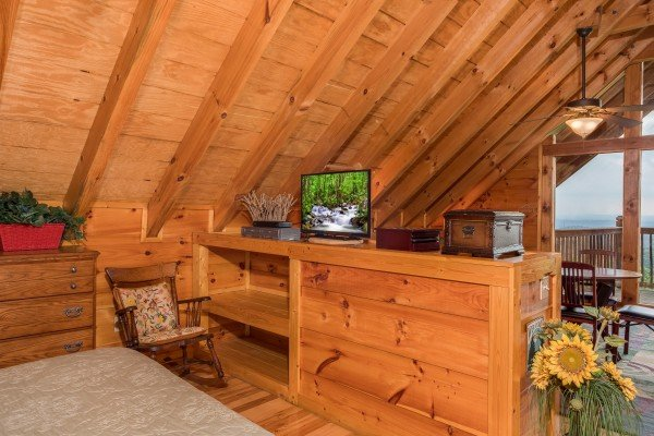 Open concept loft bedroom with a TV and built in shelves at Serenity Heights, a 3 bedroom cabin rental located in Pigeon Forge