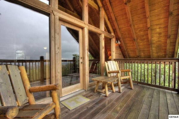 Deck with two chairs off the loft at Serenity Heights, a 3 bedroom cabin rental located in Pigeon Forge