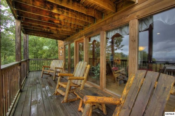 Log chairs and benches on a covered deck at Serenity Heights, a 3 bedroom cabin rental located in Pigeon Forge