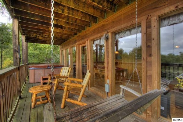 Deck with a swing, chairs, and hot tub at Serenity Heights, a 3 bedroom cabin rental located in Pigeon Forge