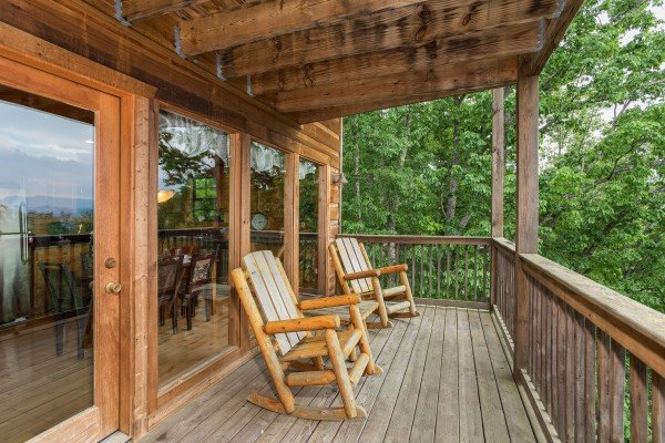 Deck with log rocking chairs at Serenity Heights, a 3 bedroom cabin rental located in Pigeon Forge