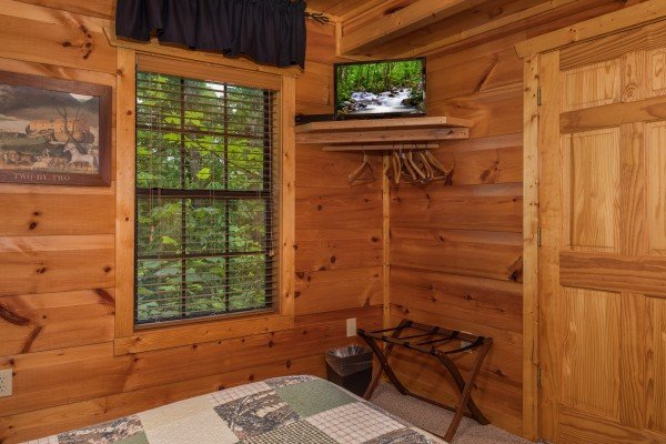 TV and suitcase stand in the queen bedroom at Serenity Heights, a 3 bedroom cabin rental located in Pigeon Forge