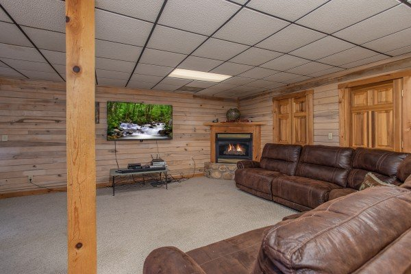 Lower level living room with a large TV and fireplace On Angels Wings, a 5 bedroom cabin rental located in Gatlinburg