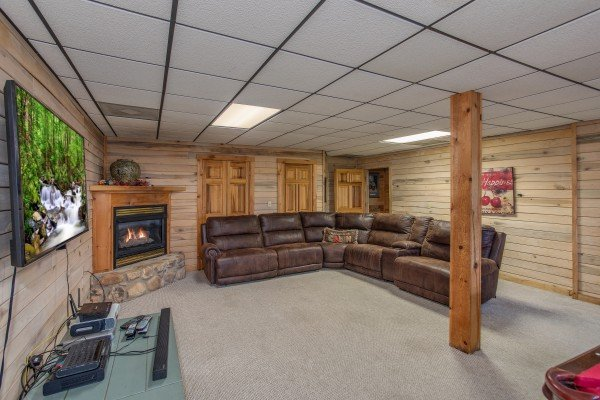Large sectional sofa, TV, and fireplace in the lower living room On Angels Wings, a 5 bedroom cabin rental located in Gatlinburg