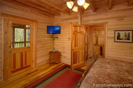 TV mounted in the corner of a main floor bedroom at On Angels Wings, a 5 bedroom cabin rental located in Gatlinburg