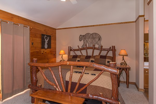 Bedroom with a wooden bed and deck access at Just for Fun, a 4 bedroom cabin rental located in Pigeon Forge