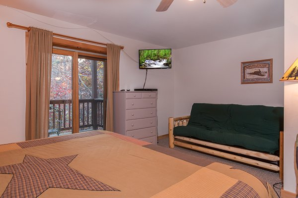 Bedroom with a futon, dresser, deck access, and TV at Just for Fun, a 4 bedroom cabin rental located in Pigeon Forge