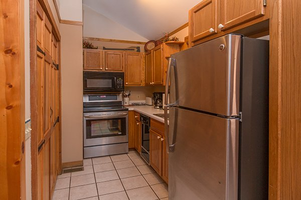 Galley kitchen with stainless appliances just off the main entrance at Just for Fun, a 4 bedroom cabin rental located in Pigeon Forge