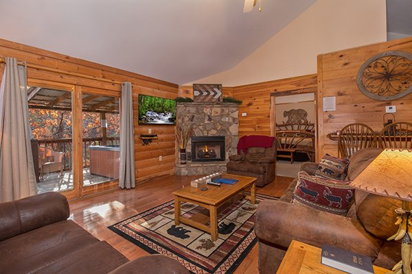 Living room with a fireplace, TV, and deck access at Just for Fun, a 4 bedroom cabin rental located in Pigeon Forge