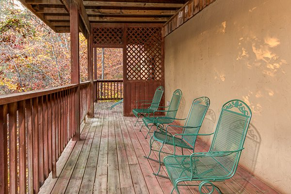 Four chairs lined up on the lower deck at Just for Fun, a 4 bedroom cabin rental located in Pigeon Forge