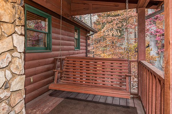 Swing on a covered porch at Just for Fun, a 4 bedroom cabin rental located in Pigeon Forge
