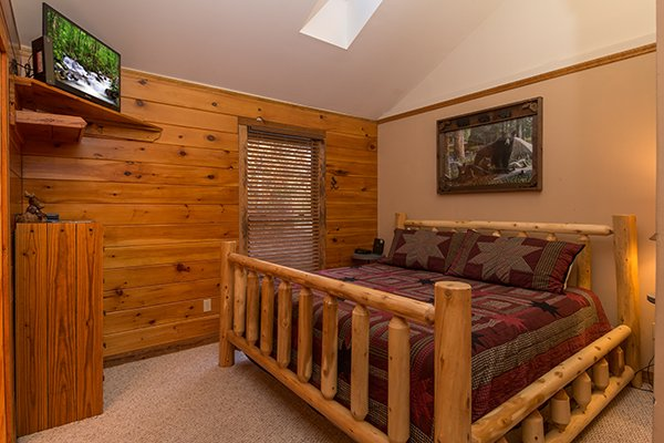 Bedroom with a king sized log bed, TV, and dresser at Just for Fun, a 4 bedroom cabin rental located in Pigeon Forge
