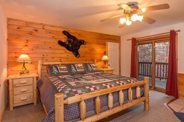 Bedroom with a king log bed, two night stands, and deck access at Just for Fun, a 4 bedroom cabin rental located in Pigeon Forge