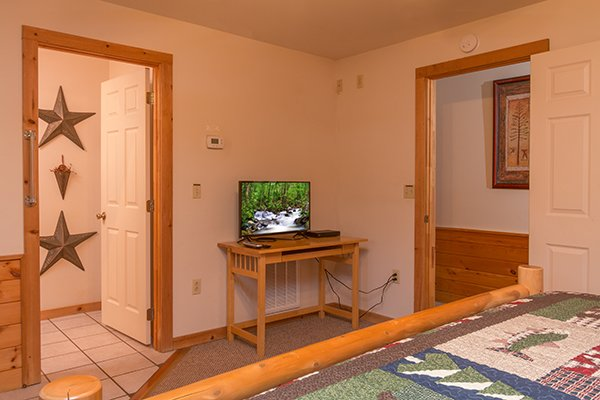 Bedroom with a writing desk and television at Just for Fun, a 4 bedroom cabin rental located in Pigeon Forge