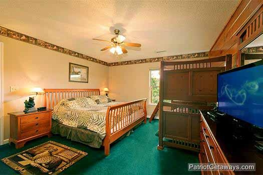 bedroom with king bed and twin bunk beds at smoky mountain lodge a 7 bedroom cabin rental located in gatlinburg