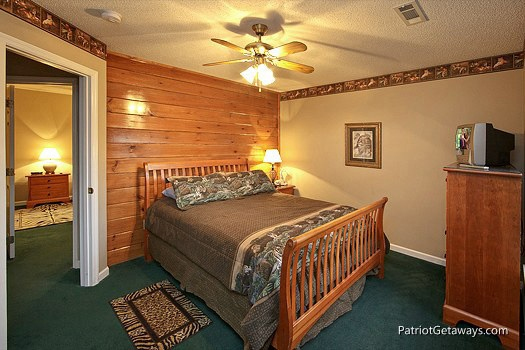 first floor bedroom with queen bed at smoky mountain lodge a 7 bedroom cabin rental located in gatlinburg