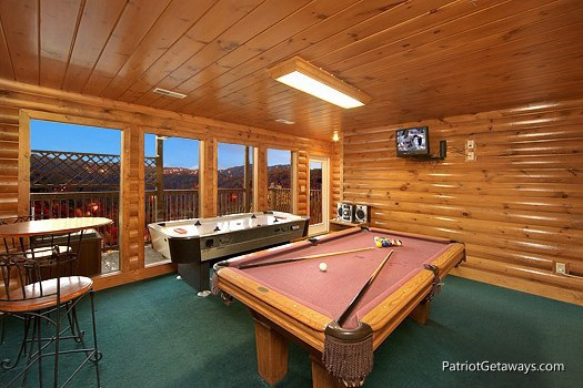 first floor game room with pool table at smoky mountain lodge a 7 bedroom cabin rental located in gatlinburg