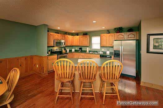 kitchen with breakfast bar at smoky mountain lodge a 7 bedroom cabin rental located in gatlinburg