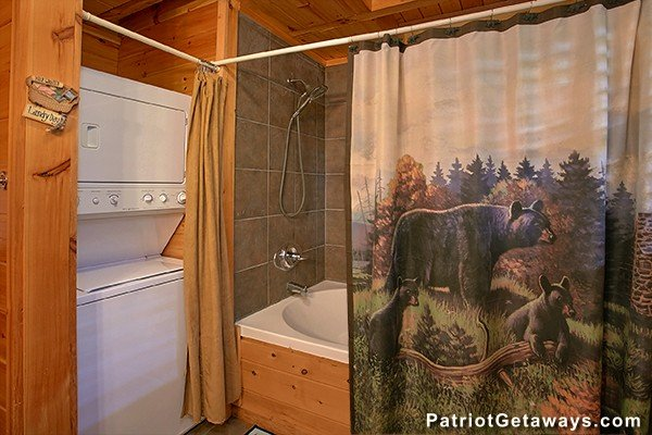 Stacked washer and dryer in a bathroom with a tub and shower at Dancin Bear Hideaway, a 2-bedroom cabin rental located in Pigeon Forge
