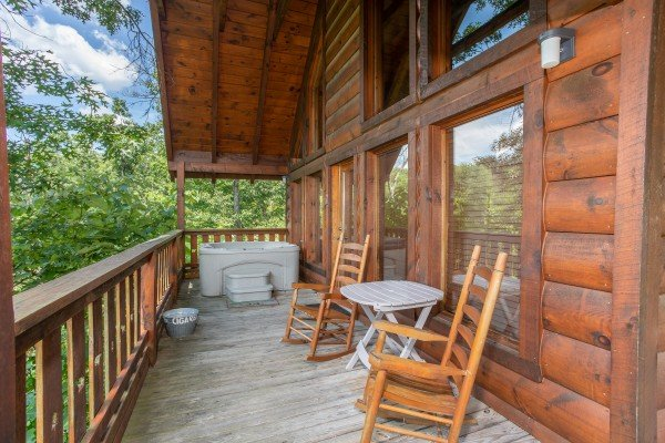Two rocking chairs and a hot tub on the covered deck at Dancin Bear Hideaway, a 2-bedroom cabin rental located in Pigeon Forge