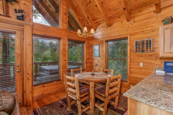 Dining table with four log chairs at Dancin Bear Hideaway, a 2-bedroom cabin rental located in Pigeon Forge