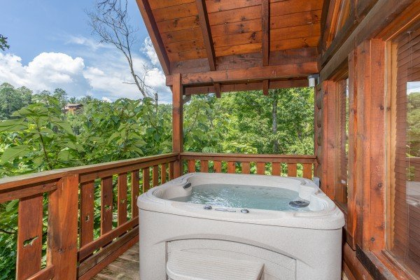 Hot tub on a covered deck with wooded views at Dancin Bear Hideaway, a 2-bedroom cabin rental located in Pigeon Forge