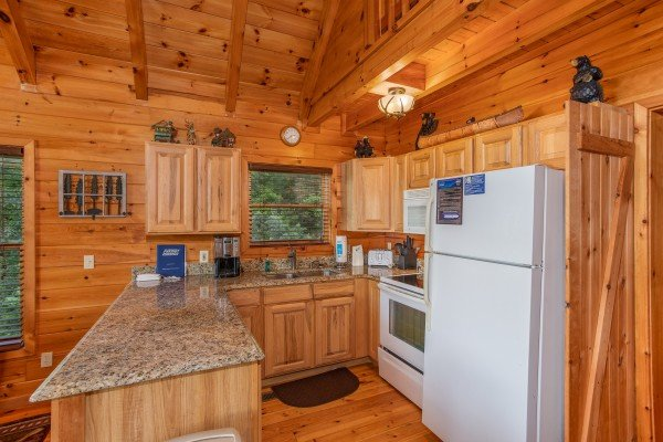 Kitchen with white appliances at Dancin Bear Hideaway, a 2-bedroom cabin rental located in Pigeon Forge