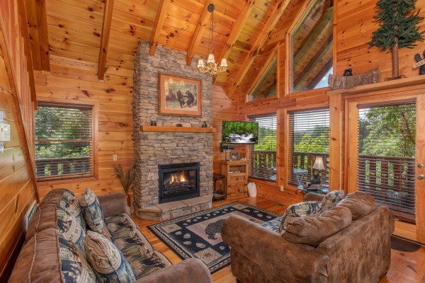 Living room with a stone fireplace, TV, sofa, loveseat, and large windows at Dancin Bear Hideaway, a 2-bedroom cabin rental located in Pigeon Forge