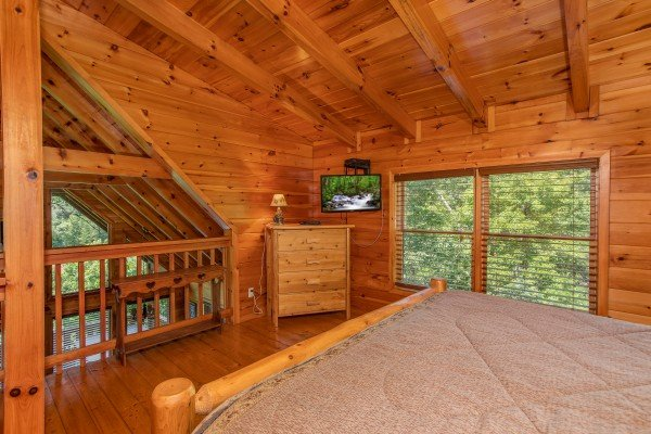 Loft bedroom with a king bed, dresser, TV, and views to the lower floor at Dancin Bear Hideaway, a 2-bedroom cabin rental located in Pigeon Forge