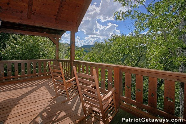 Two rocking chairs on a covered deck looking at the trees and views Dancin Bear Hideaway, a 2-bedroom cabin rental located in Pigeon Forge