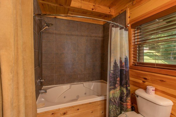 Tub and shower at Dancin Bear Hideaway, a 2-bedroom cabin rental located in Pigeon Forge
