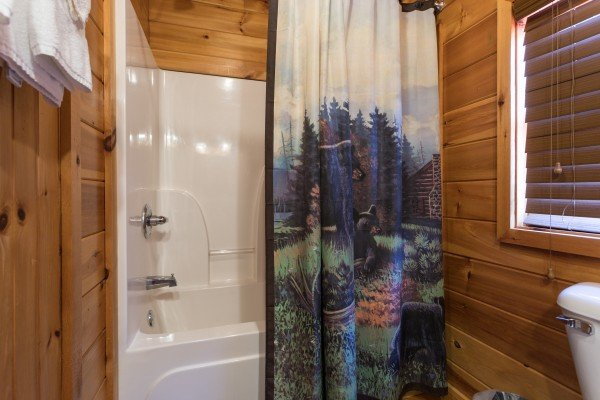 Bathroom with a tub and shower at Dancin Bear Hideaway, a 2-bedroom cabin rental located in Pigeon Forge