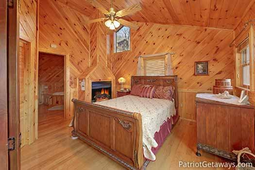 Queen sized bed next to fireplace in a bedroom at Kaleidoscope, a 2 bedroom cabin rental located in Pigeon Forge