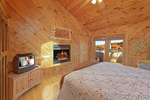 Bedroom with fireplace at foot of bed at Kaleidoscope, a 2 bedroom cabin rental located in Pigeon Forge