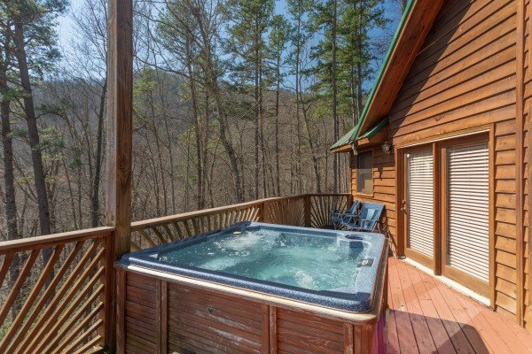 Hot tub and seating on the deck at Kaleidoscope, a 2 bedroom cabin rental located in Pigeon Forge