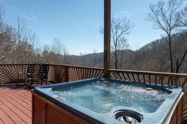 Hot tub on the covered deck at Kaleidoscope, a 2 bedroom cabin rental located in Pigeon Forge