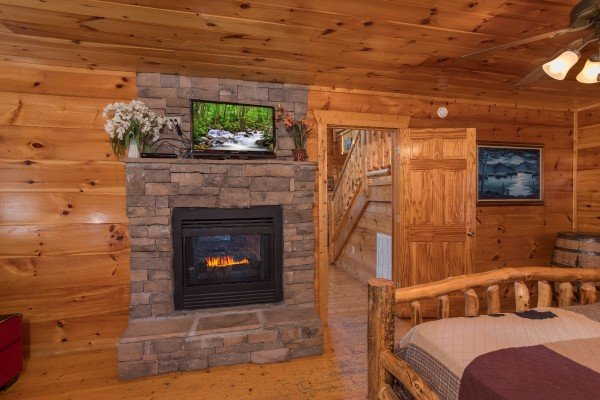 Fireplace and TV in the king bedroom at Moonshine Memories, a 2 bedroom cabin rental located in Gatlinburg