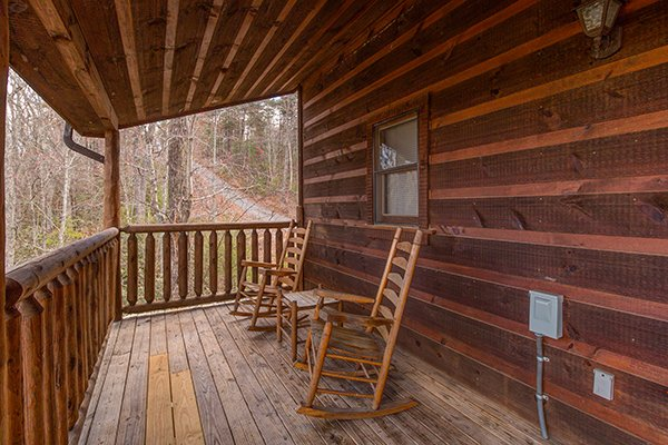 Covered deck with rocking chairs at Moonshine Memories, a 2 bedroom cabin rental located in Gatlinburg
