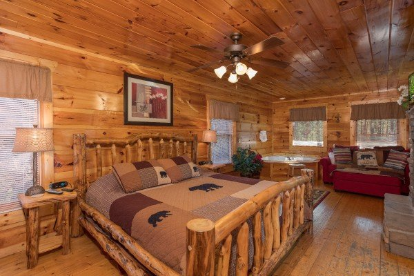 Bedroom with a king-sized log bed and corner jacuzzi at Moonshine Memories, a 2 bedroom cabin rental located in Gatlinburg