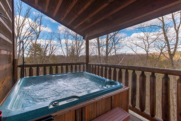Hot tub on a covered deck at Moonshine Memories, a 2 bedroom cabin rental located in Gatlinburg