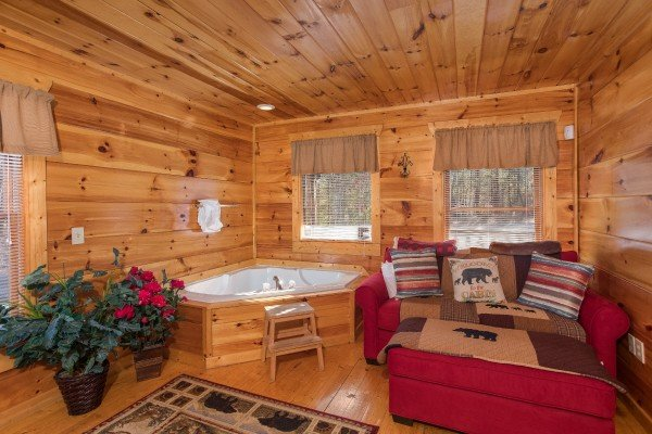 Corner jacuzzi tub and sofa bed in the king bedroom at Moonshine Memories, a 2 bedroom cabin rental located in Gatlinburg