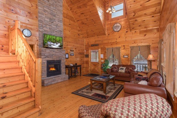 Living room with a fireplace, TV, and high ceilings at Moonshine Memories, a 2 bedroom cabin rental located in Gatlinburg